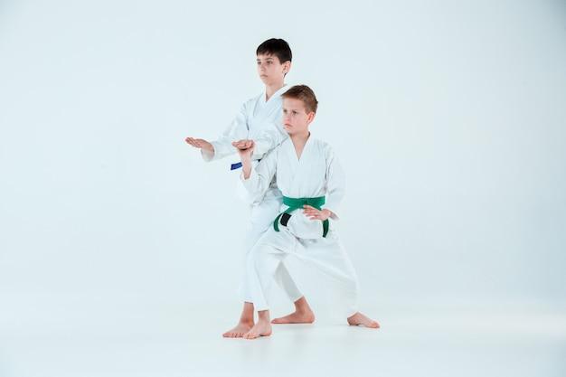 Chłopcy pozujący na treningu aikido w szkole sztuk walki. pojęcie zdrowego stylu życia i sportu