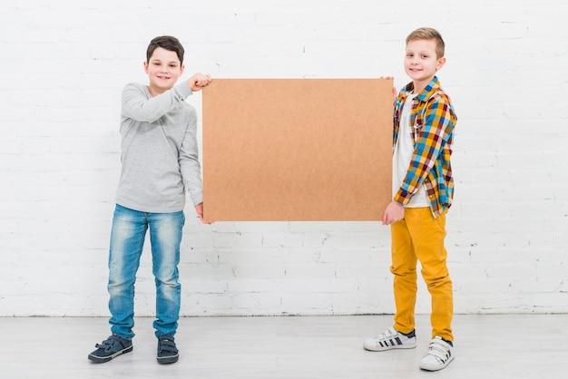 Chłopcy prezentujący dużą deskę
