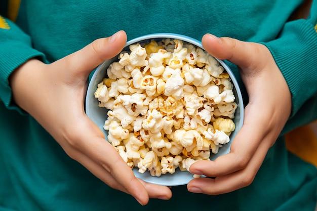 Chłopcy ręce i miska popcornu z bliska