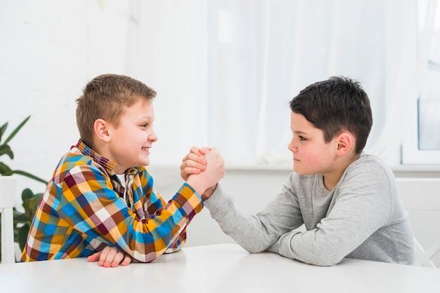 Chłopcy robią siłowanie się na rękę