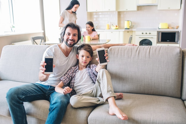Chłopcy siedzą na kanapie i trzymają telefon w rękach