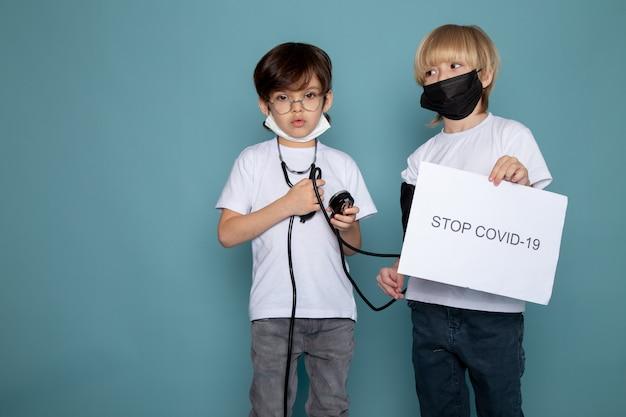 Chłopcy słodkie urocze w maskach ochronnych, trzymając stop covid puste na niebieską ścianą