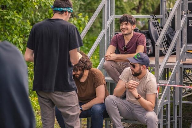 Chłopcy śmieją się i żartują siedząc na schodach w parku na świeżym powietrzu
