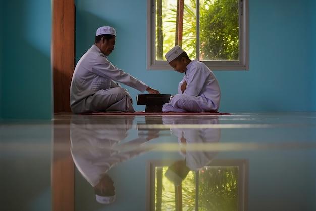 Chłopcy uczą się czytać koran od starszych w meczecie, pojęcie nowej generacji islamu.