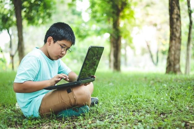 Chłopcy uczą się w szkole podstawowej, noszą okulary, obserwują czarne notebooki siedzące na trawniku w ogrodzie.