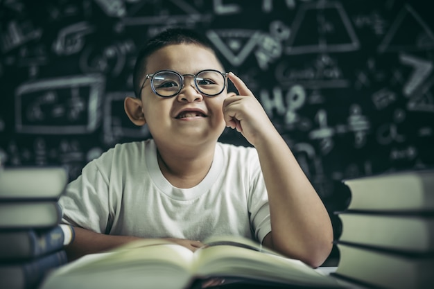 Chłopcy w okularach piszą książki i myślą w klasie