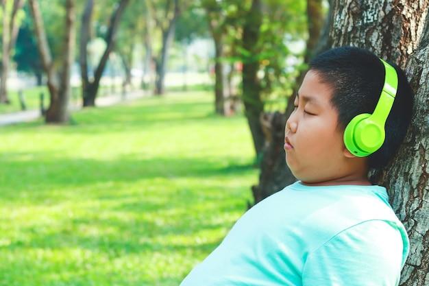 Chłopcy w zielonych słuchawkach stojących pod drzewem, z zamkniętymi oczami, szczęśliwi