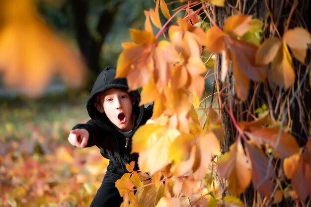 Chłopcy wychylają się zza drzewa pokrytego jesiennymi liśćmi.