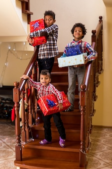 Chłopcy z prezentami na schodach troje dzieci trzymających prezenty świąteczne ulubione święto dzieci...