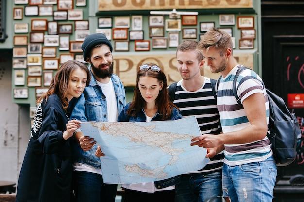 Chłopcy z torbami i dziewczynami patrzą na mapę turystyczną stojącą gdzieś na starym mieście