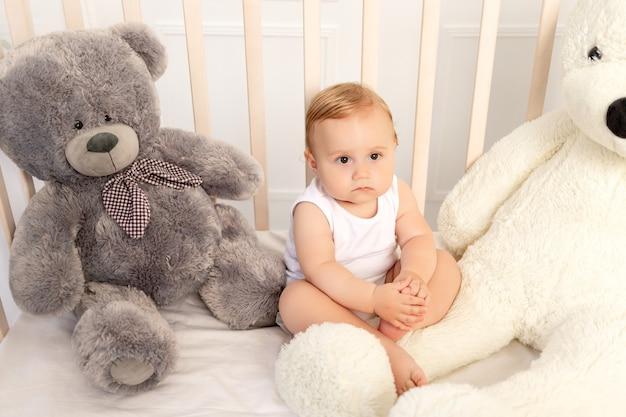 Chłopczyk 1 rok siedzący w łóżeczku z dużymi misiami, dziecko w żłobku.