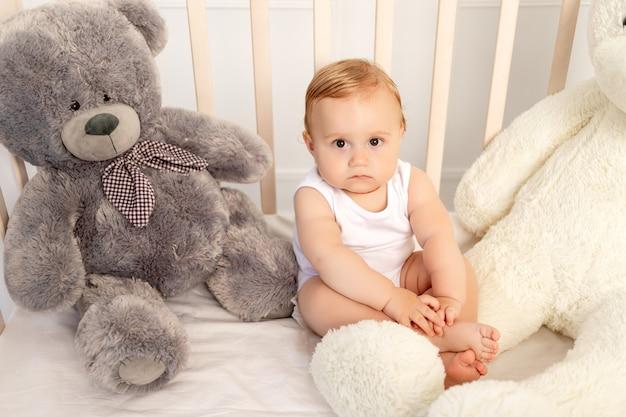 Chłopczyk 1 rok siedzi w łóżeczku z dużymi misiami, dziecko w żłobku