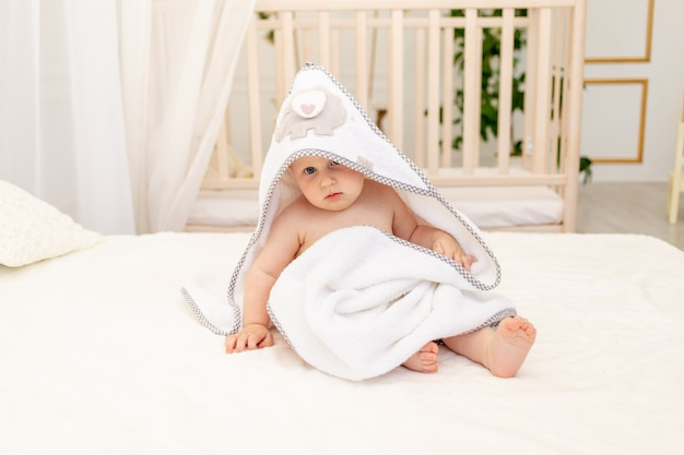 Chłopczyk 8 miesięcy siedzi na białym łóżku w białym ręczniku po kąpieli w łazience w domu