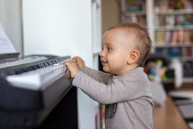 Chłopczyk chce grać na pianinie w domu, dziecko lubi muzykę klasyczną.