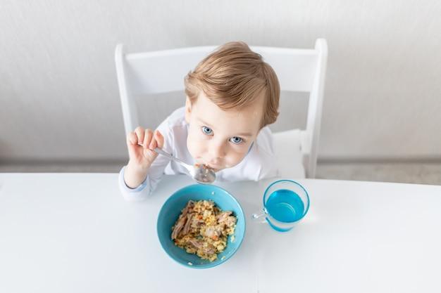 Chłopczyk je łyżką w domu, koncepcja jedzenia i żywienia dla dzieci