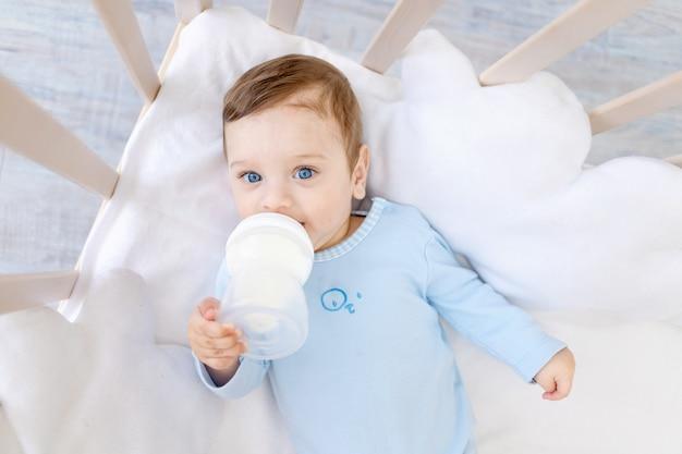 Chłopczyk jedzący z butelki mleka w łóżeczku w niebieskim body, słodkie małe dziecko w sypialni, koncepcja jedzenia dla niemowląt