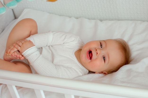 Chłopczyk leży w łóżeczku w dziecięcej sypialni