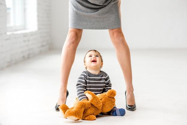 Chłopczyk patrzący w górę w pobliżu pięknych nóg kobiety siedzącej na podłodze