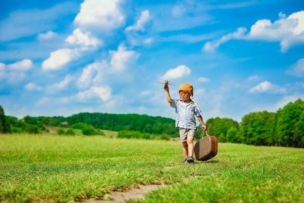 Chłopczyk przy samolocie bawi się na łonie natury w parku. chłopiec na wakacyjnym pilocie.