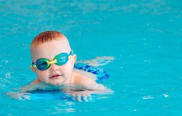 Chłopczyk samodzielnie pływa w basenie.