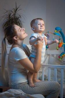 Chłopczyk siedzi na kolanach matki w sypialni w nocy