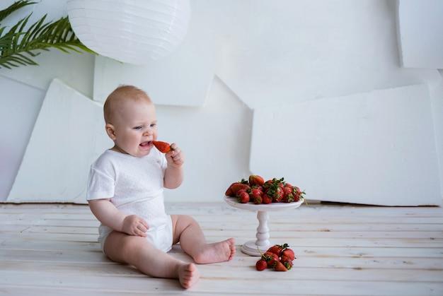 Chłopczyk siedzi w białym body i zjada kilka truskawek na białej ścianie z miejscem na tekst
