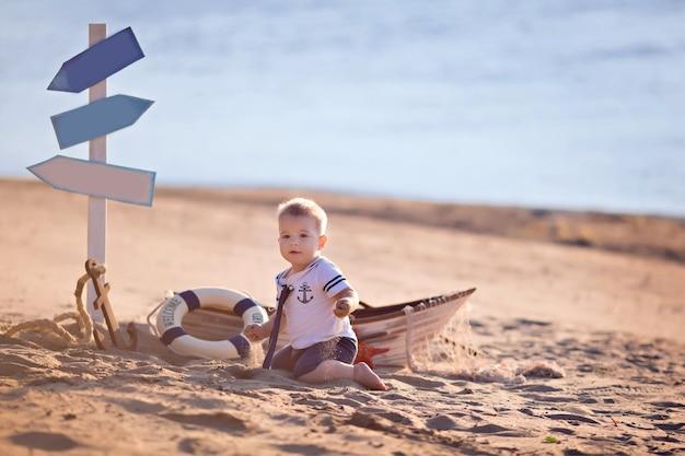 Chłopczyk siedzi w łodzi, przebrany za marynarza, na piaszczystej plaży z muszelkami nad morzem