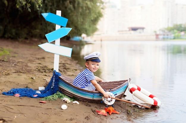 Chłopczyk siedzi w łodzi, przebrany za marynarza na piaszczystej plaży z muszelkami nad morzem