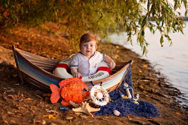 Chłopczyk siedzi w łodzi przebrany za marynarza