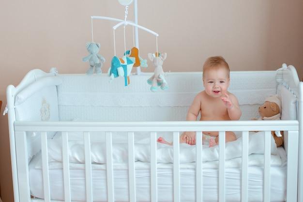 Chłopczyk siedzi w łóżeczku niemowlęcym w pieluszce