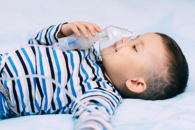 Chłopczyk trzymający maskę z rozpylaczem immobilizera podczas oddychania