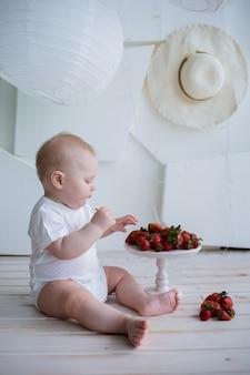 Chłopczyk w białym body siedzi z talerzem truskawek na białej ścianie z miejscem na tekst