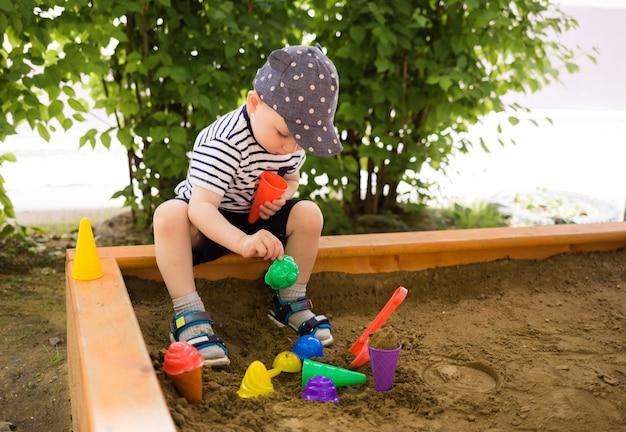 Chłopczyk w czapce bawi się w piaskownicy z foremkami do piasku. letnie zabawy dla dzieci