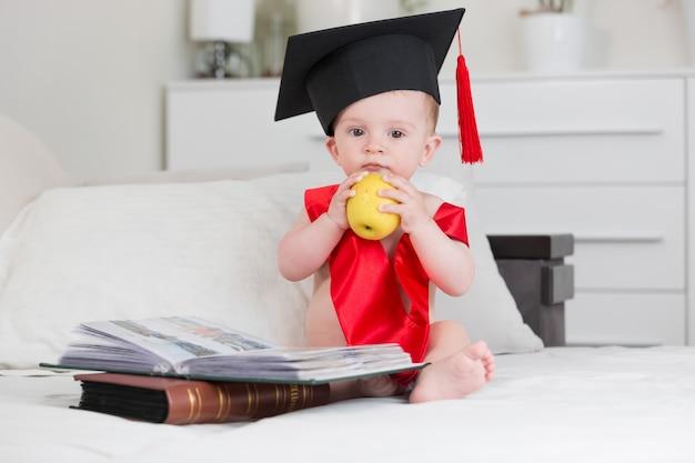 Chłopczyk w czapce dyplomowej siedzący na kanapie z książkami