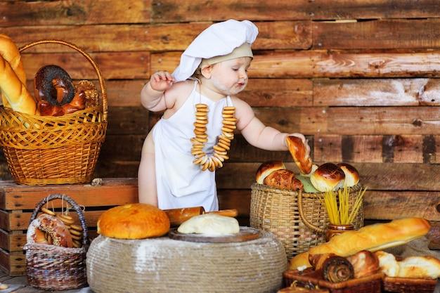 Chłopczyk w czapce i fartuchu kucharza z bukietem bajgli na szyi siedzi na tle produktów piekarniczych w sklepie z chlebem