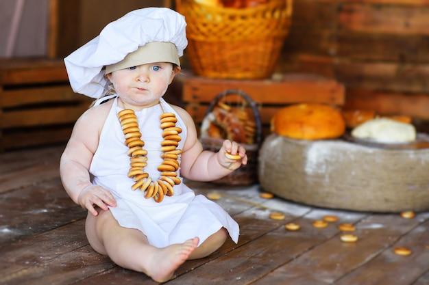 Chłopczyk w czapce i fartuchu kucharza z bukietem bajgli wokół szyi na drewnianym tle