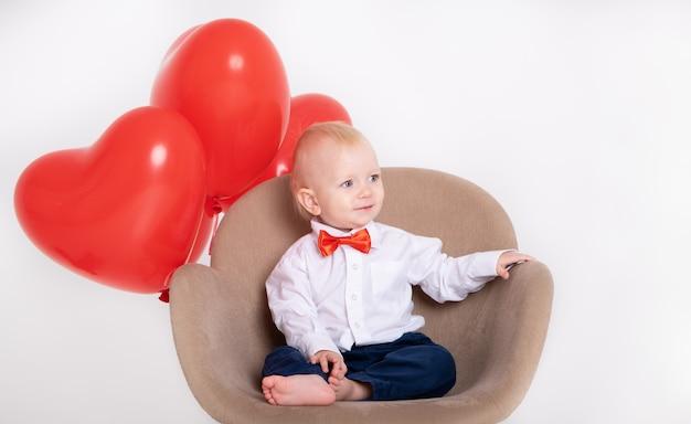Chłopczyk w garniturze i czerwona muszka trzyma balony w kształcie serca siedzi na krześle
