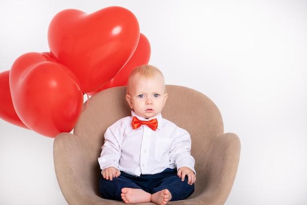 Chłopczyk w garniturze i czerwonej muszce trzyma balony w kształcie serca siedzi na krześle na białej ścianie.