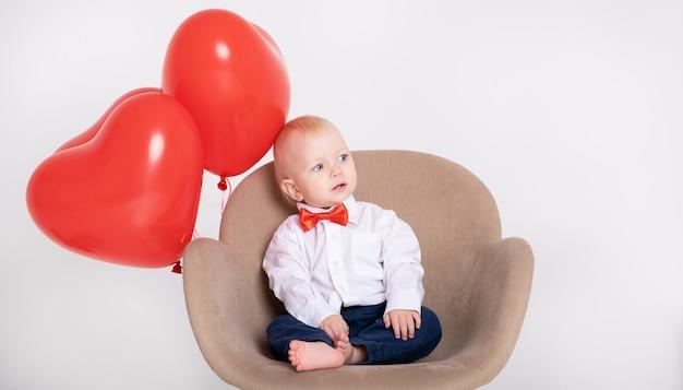 Chłopczyk w garniturze i czerwonej muszce trzyma bukiet róż siedzi na krześle na białej ścianie.