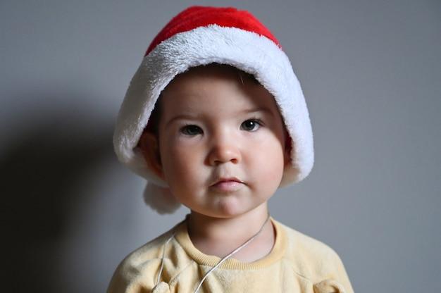 Chłopczyk w kapeluszu boże narodzenie na szarym tle