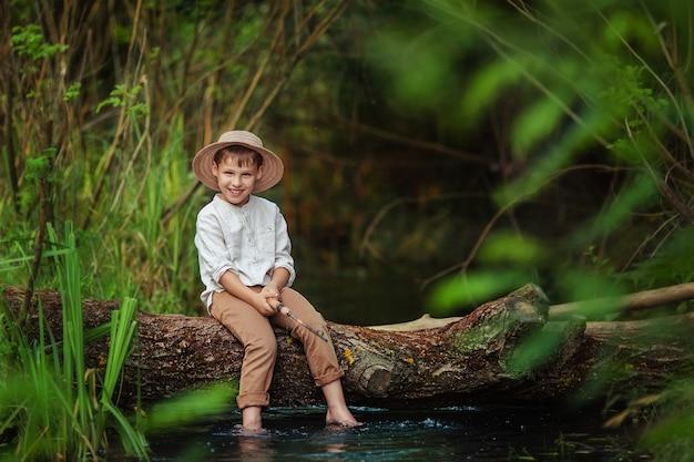 Chłopczyk w rustykalnym ubraniu i wiklinowym kapeluszu siedzi z wędką w rękach i łapie rybę na pniu po drugiej stronie rzeki. hobby i wypoczynek dla mężczyzn.