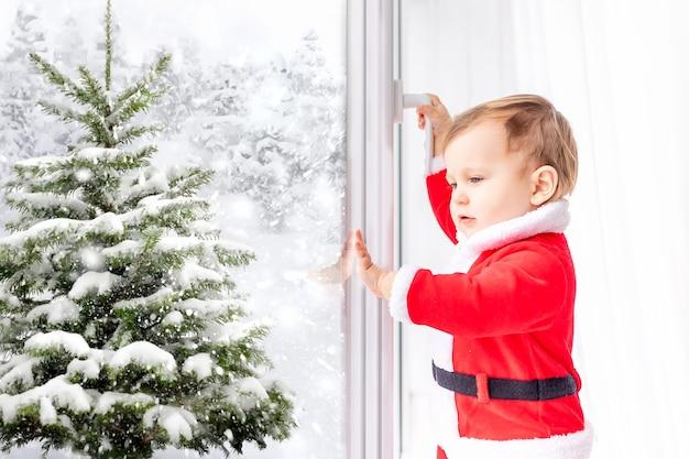 Chłopczyk w stroju świętego mikołaja wygląda i otwiera okno zimą na ośnieżoną choinkę, koncepcja nowego roku i bożego narodzenia