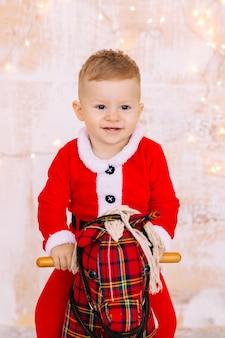 Chłopczyk w świątecznym stroju na ścianie konia na biegunach z girlandami. ścieśniać.