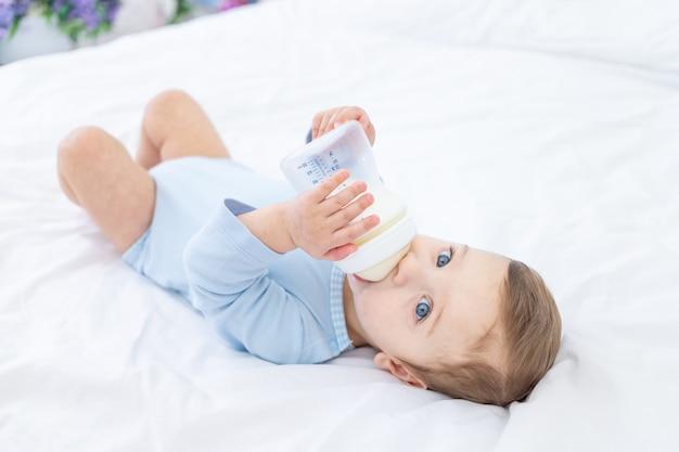 Chłopczyk z butelką mleka na łóżku do spania w niebieskim body, koncepcja jedzenia dla niemowląt