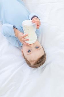 Chłopczyk z butelką mleka na łóżku przed pójściem spać w niebieskim body, koncepcja jedzenia dla niemowląt