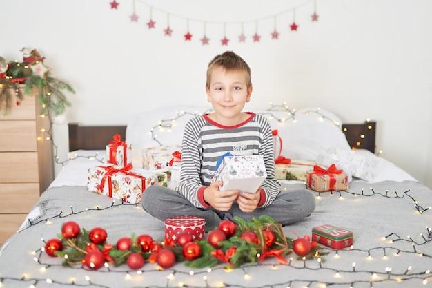 Chłopczyk z prezentami świątecznymi w domu na łóżku z wystrojem świątecznym