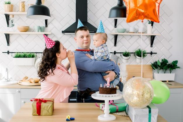 Chłopczyk z rodzicami w jasnych czapkach urodzinowych z okazji pierwszych urodzin z ciastem, prezentami, imprezowymi rogami i balonami w domu