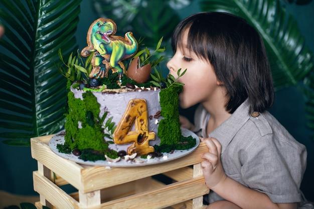 Chłopczyk zjada ciasto z ugryzieniem w dniu swoich urodzin