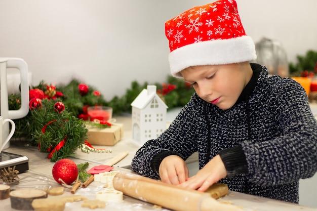 Chłopiec 7-10 w świątecznej czapce mikołaja, robiąc świąteczne pierniki w noworocznej kuchni.