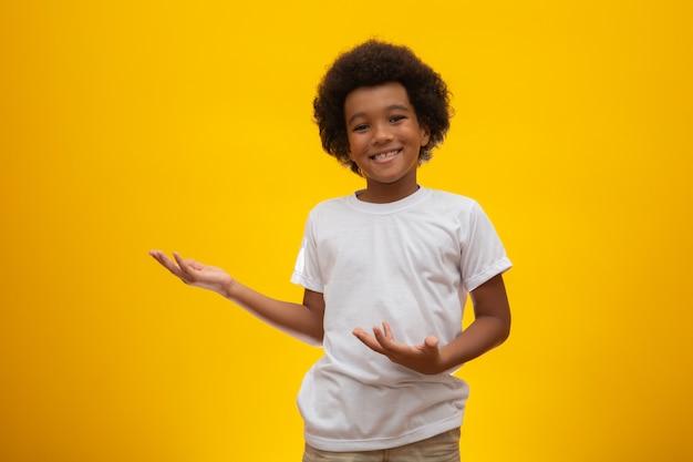 Chłopiec afroamerykanów z czarnymi włosami moc na żółty. uśmiechający się czarny dzieciak z czarnymi włosami mocy. czarny chłopiec z czarnymi włosami mocy. afrykańskie pochodzenie.